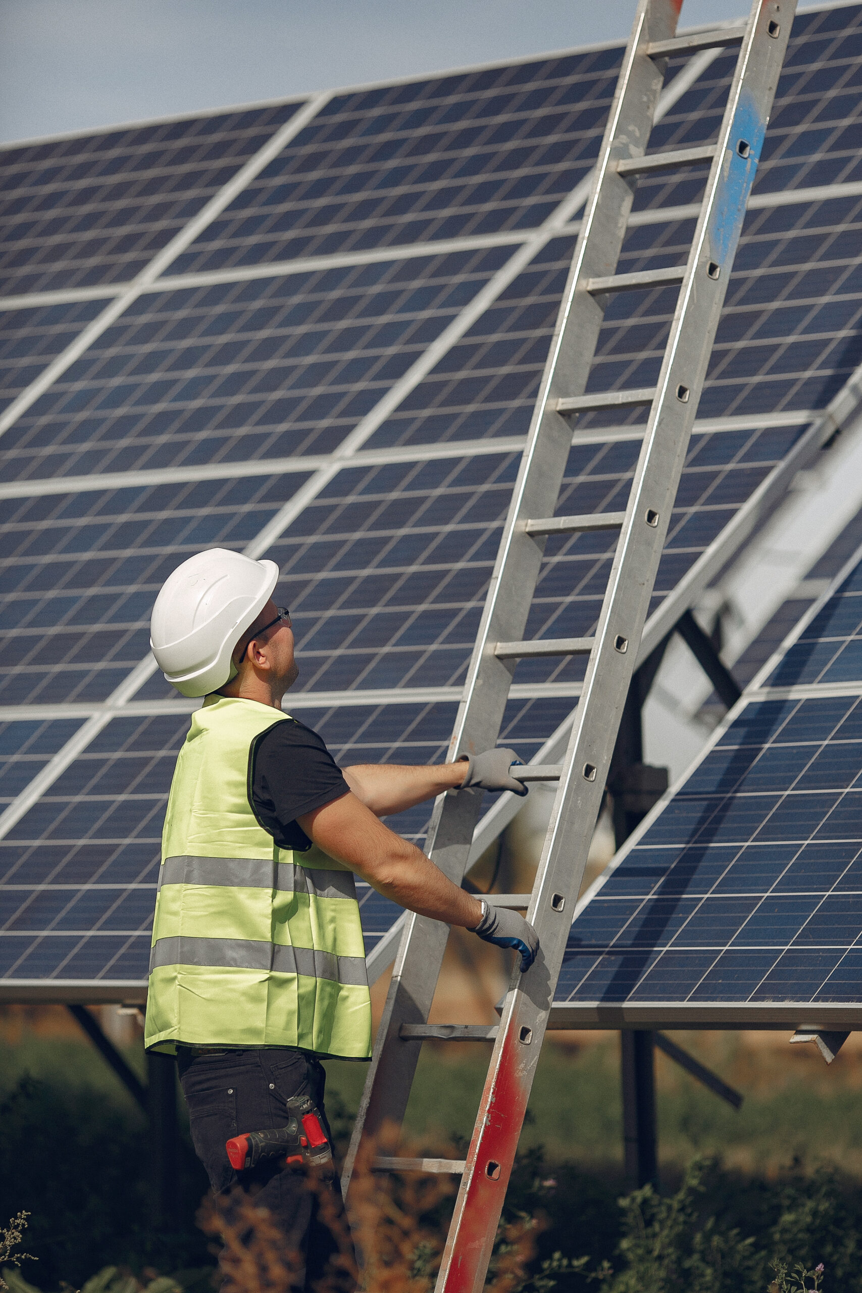 Engineer in a white helmet. Man near solar panel. Worker with a ladder